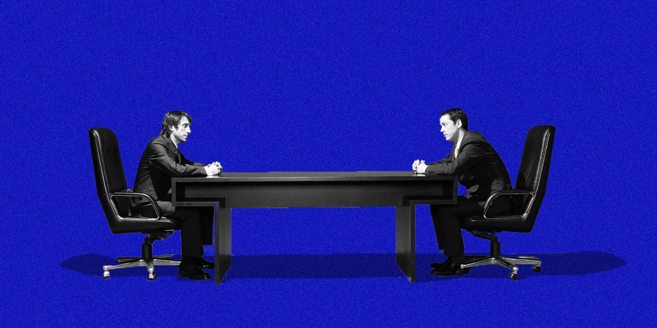 two men in business suits facing each other at opposite ends of a long conference table